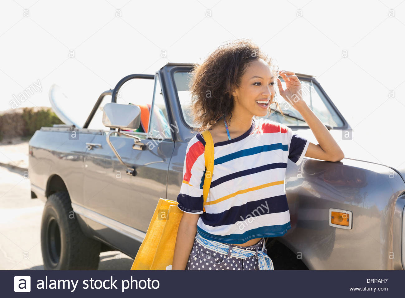 Smiling woman leaning against off-road vehicle - Stock Image