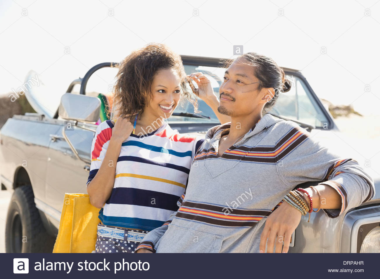 Multiethnic couple leaning against off-road vehicle - Stock Image