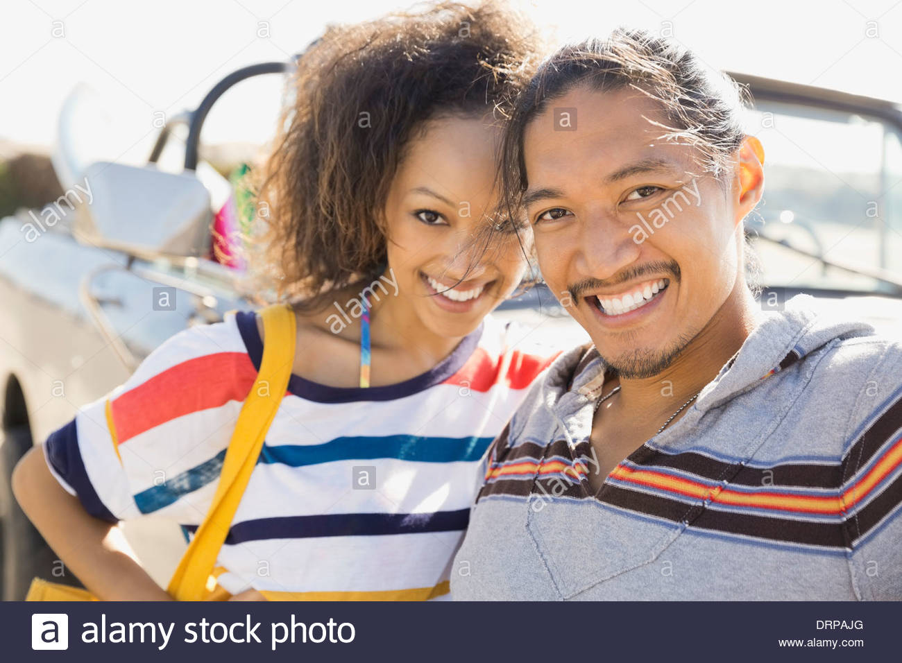Portrait of multiethnic couple standing by off-road vehicle - Stock Image