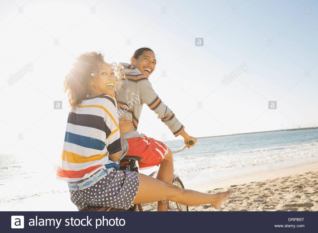 Couple enjoying bicycle ride on beach - Stock Image