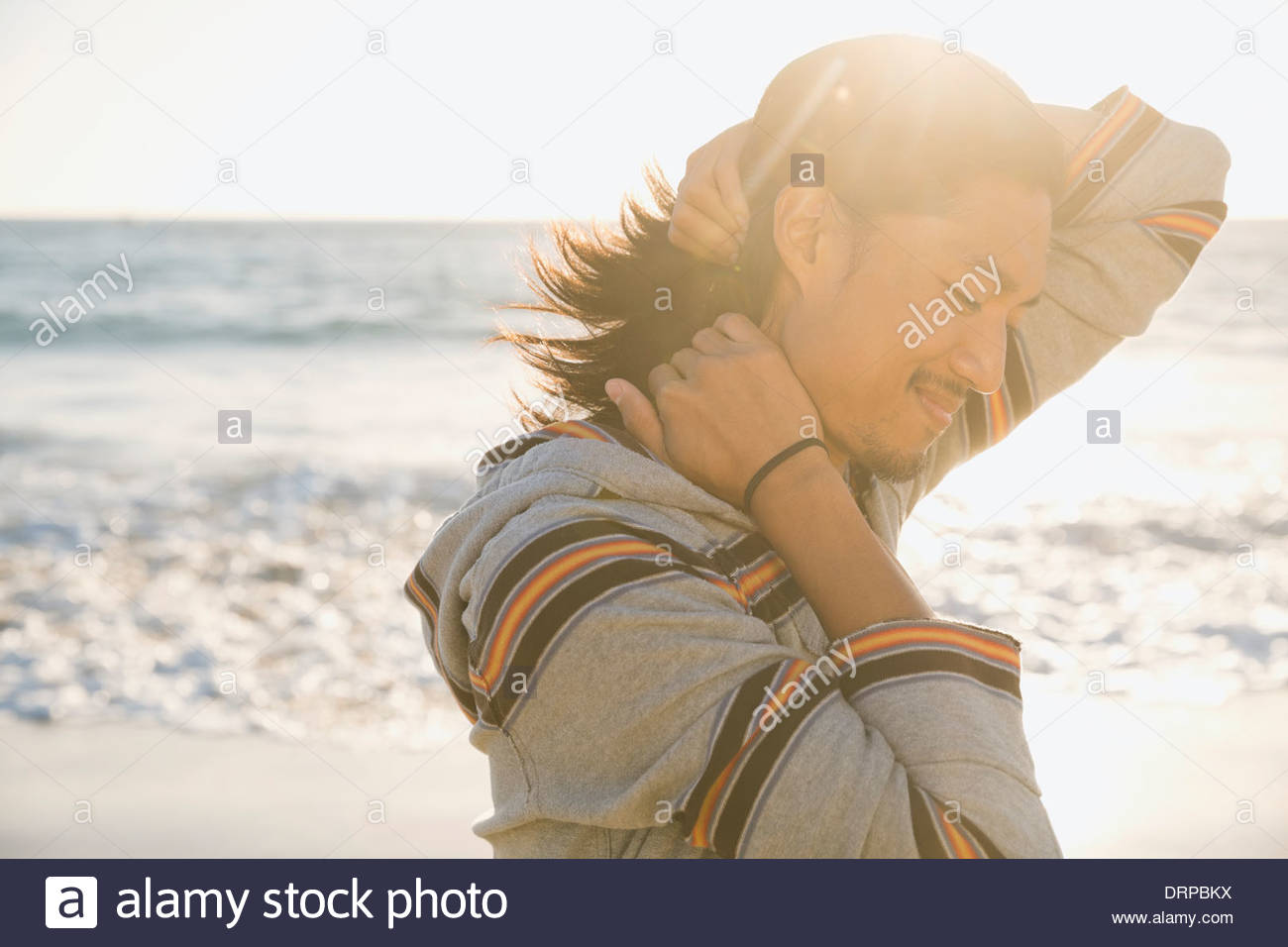 Smiling man standing near the ocean - Stock Image