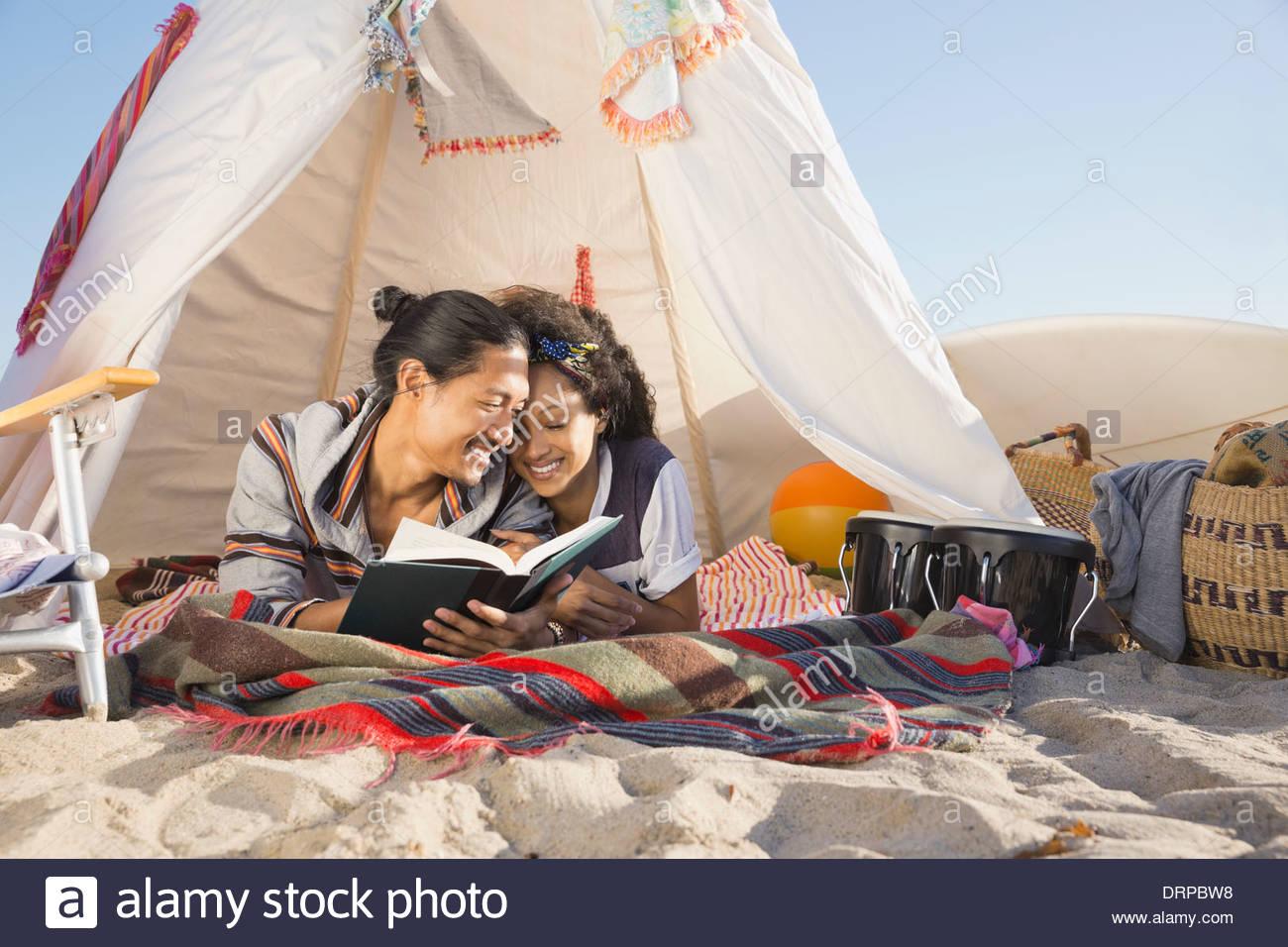 Romantic couple reading book on beach - Stock Image