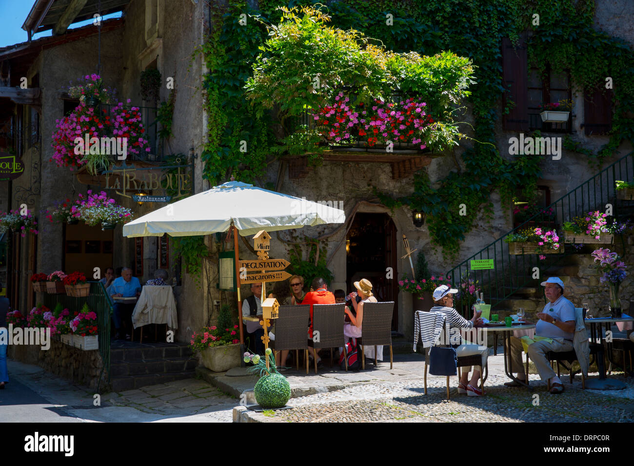 Diners at restaurant cafe La Raboue in the historic medieval district of Yvoire by Lac Leman, Lake Geneva, France - Stock Image