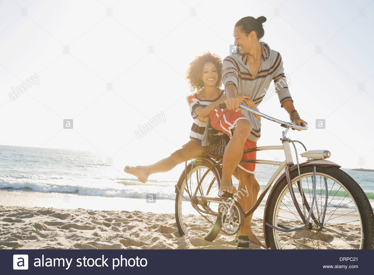 Couple enjoying bicycle ride on beach - Stock Image