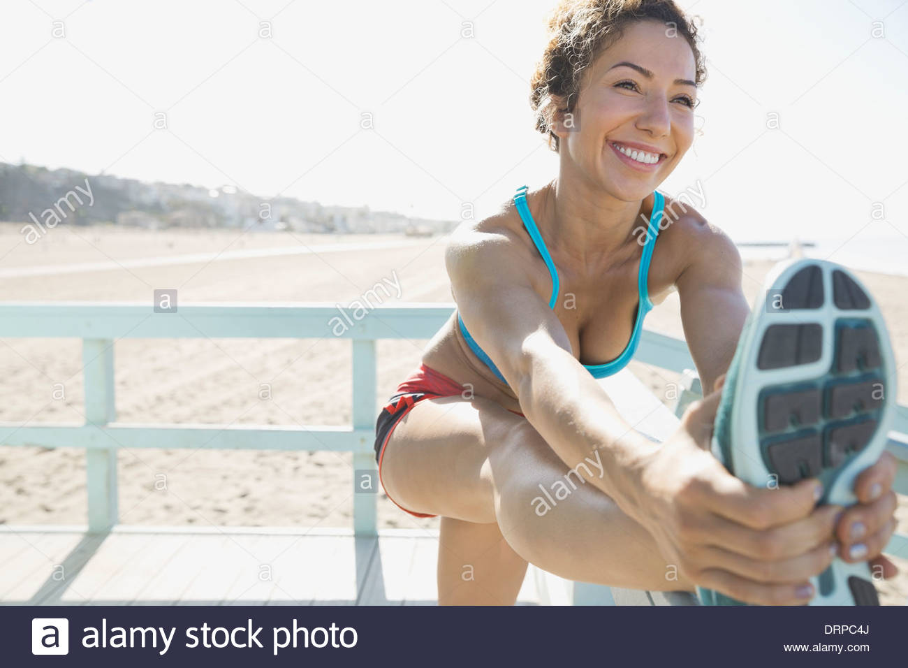 Woman stretching legs before workout - Stock Image