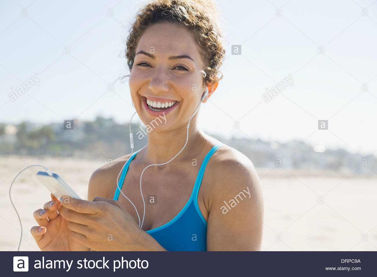 Portrait of active woman listening to music at beach - Stock Image