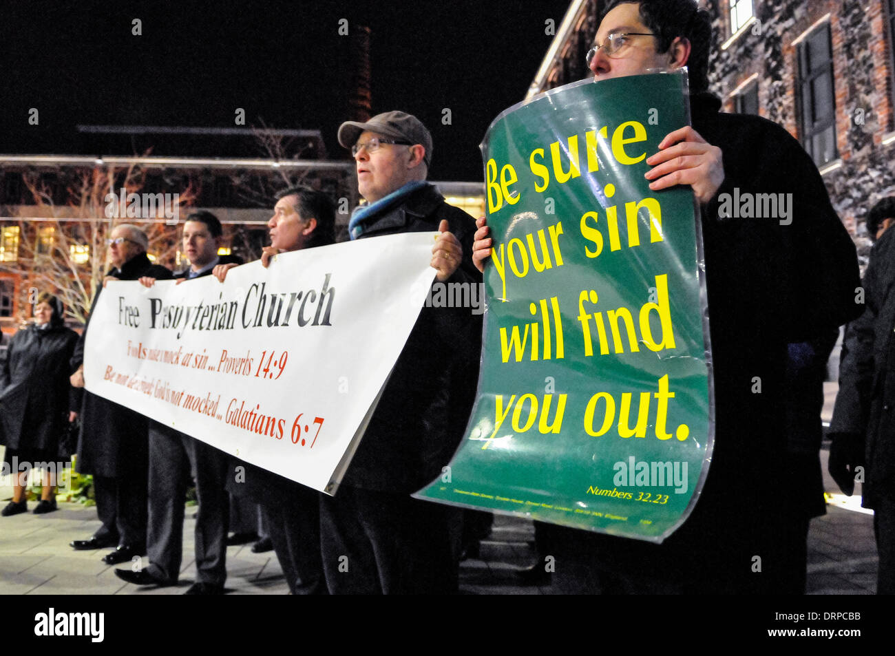"""Newtownabbey, Northern Ireland. 30 Jan 2014  - Protesters from the Free Presbyterian Church hold posters saying """"Be sure your sin will find you out"""", while they sing hymns outside a theatre, which is hosting a play they consider to be 'blasphemous' Credit:  Stephen Barnes/Alamy Live News Stock Photo"""