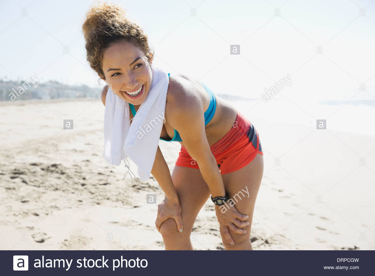 Active woman resting after workout on the beach - Stock Image