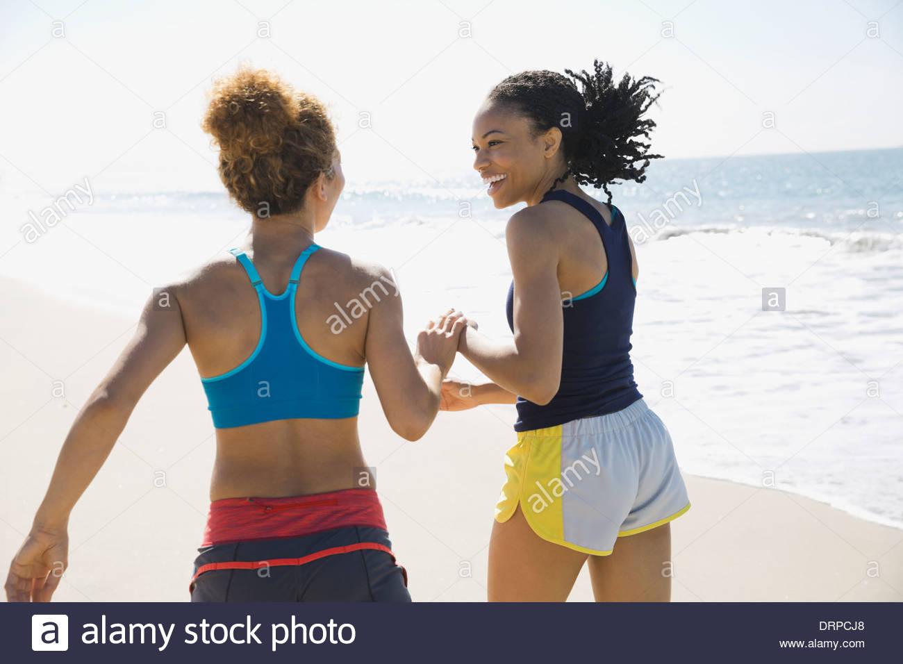 Female friends jogging on beach - Stock Image