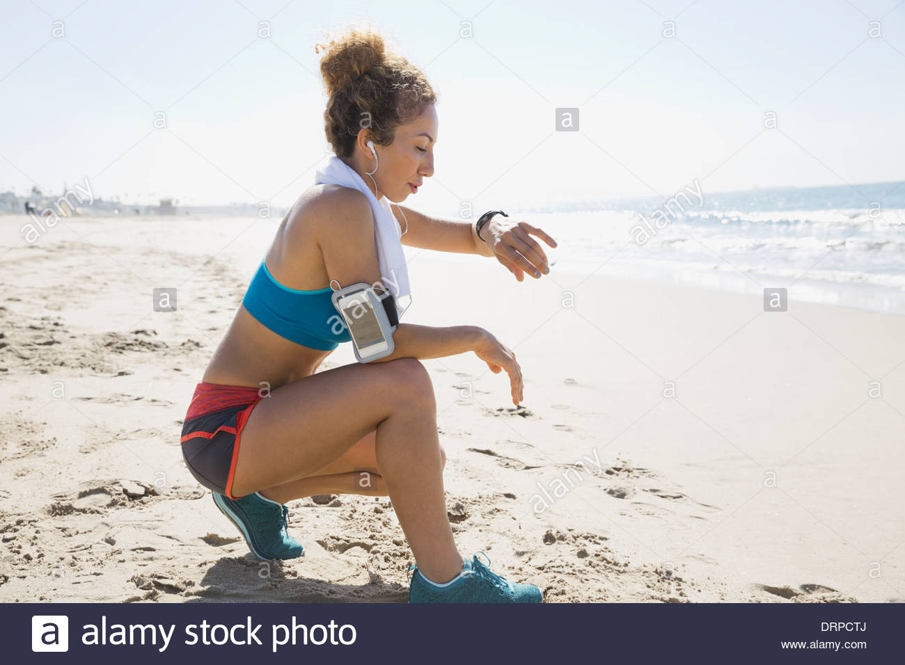 Active woman timing rest period with stopwatch - Stock Image