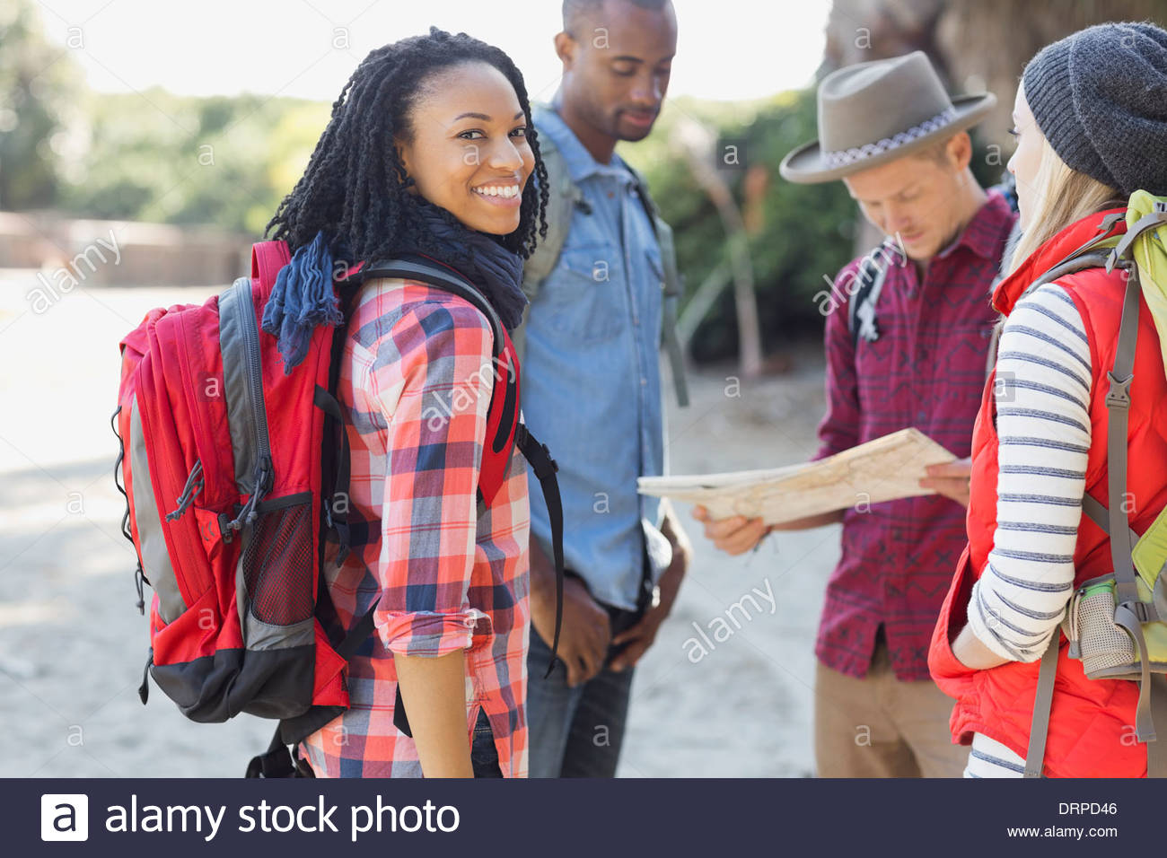 Portrait of female backpacker with friends outdoors - Stock Image