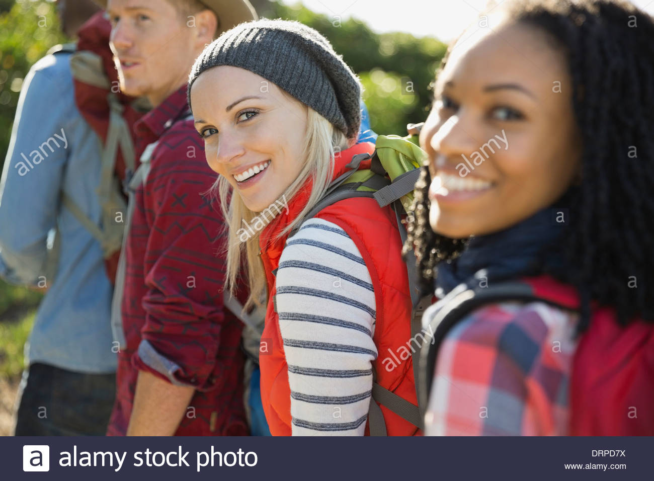 Portrait of female backpacker with group of friends - Stock Image