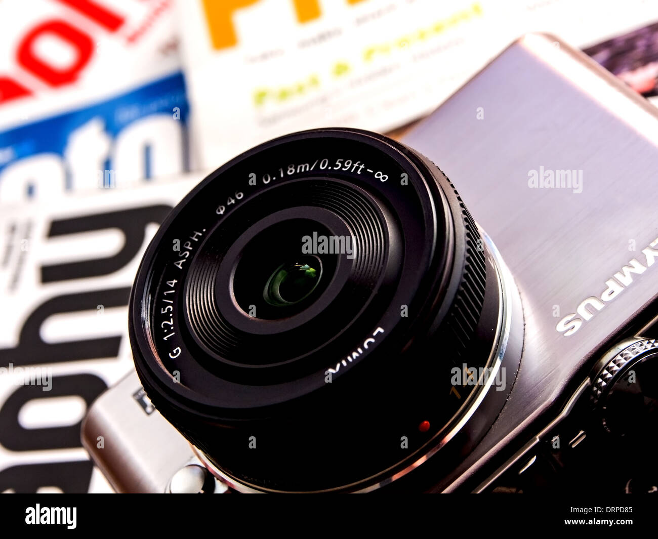 Compact system camera with scattered photography magazines - Stock Image