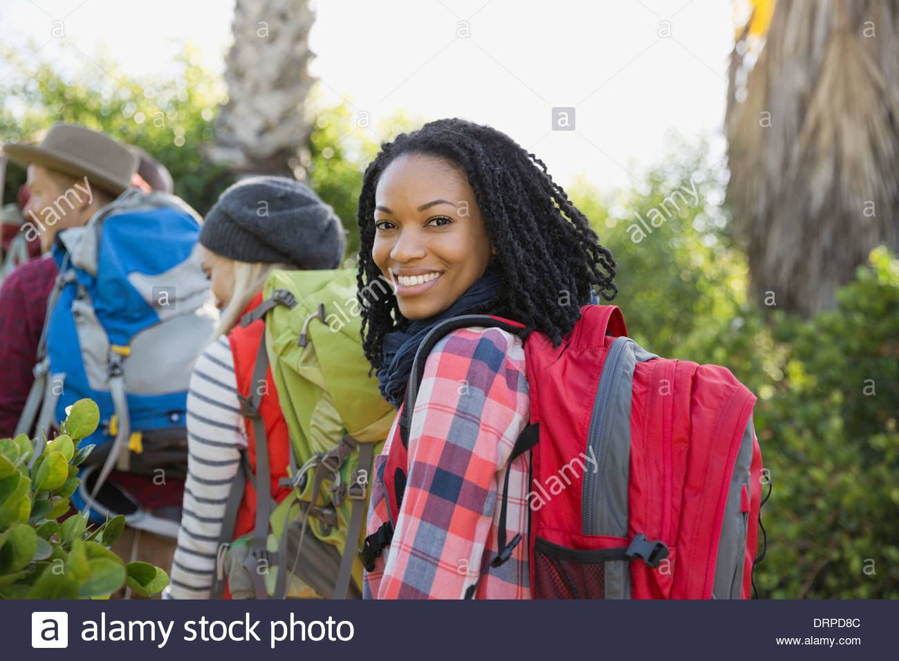 Portrait of confident woman backpacking with group - Stock Image