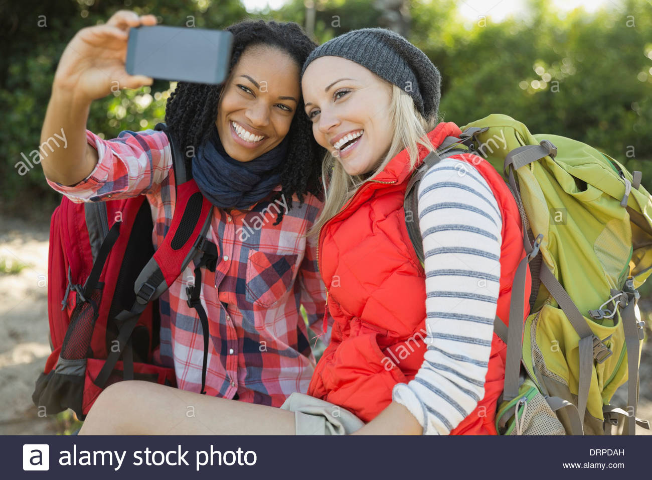 Female backpackers taking self portrait with smart phone - Stock Image