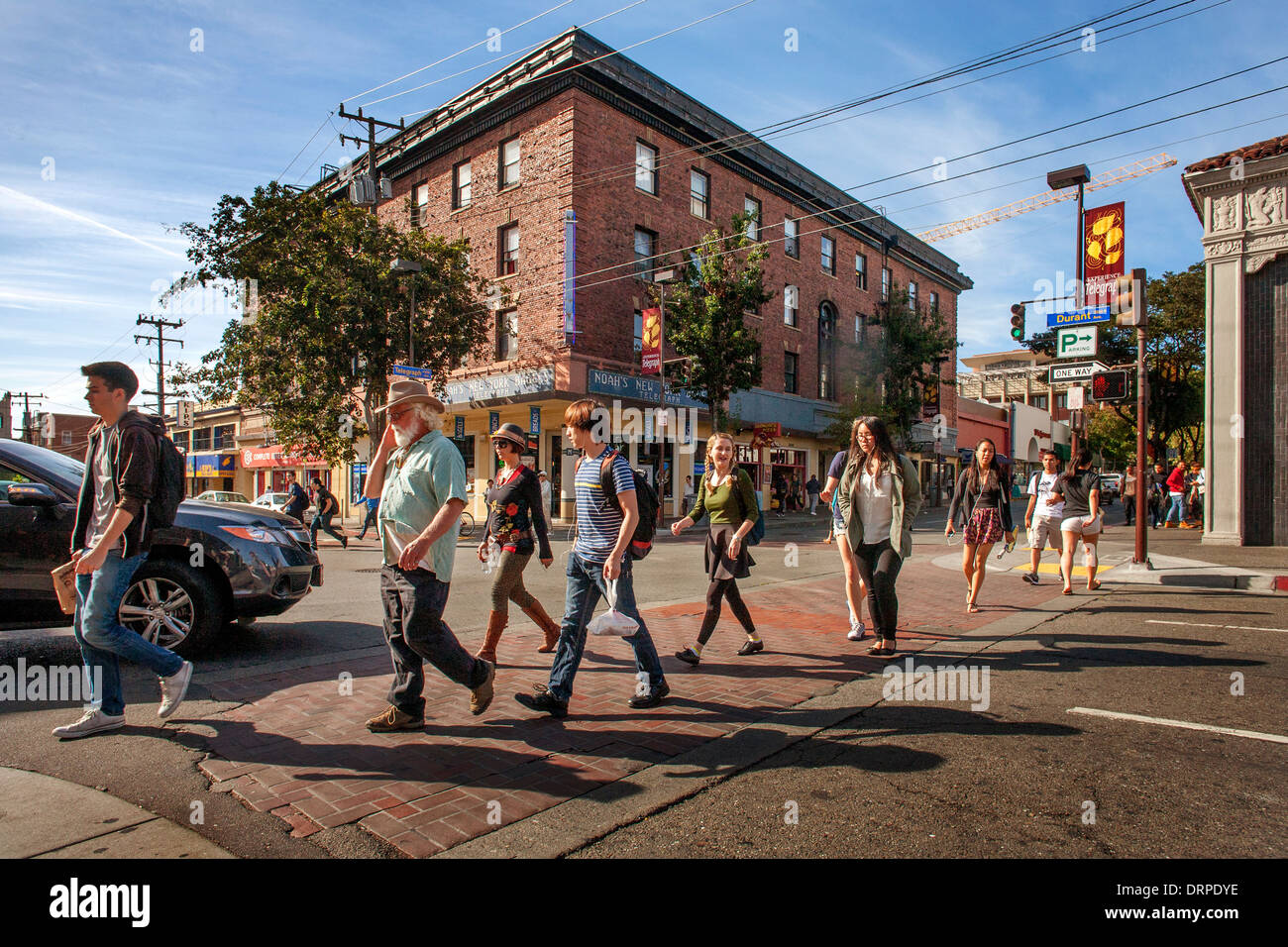 Multiracial University of California students and older locals walk across Durant Avenue in Berkeley, CA. - Stock Image