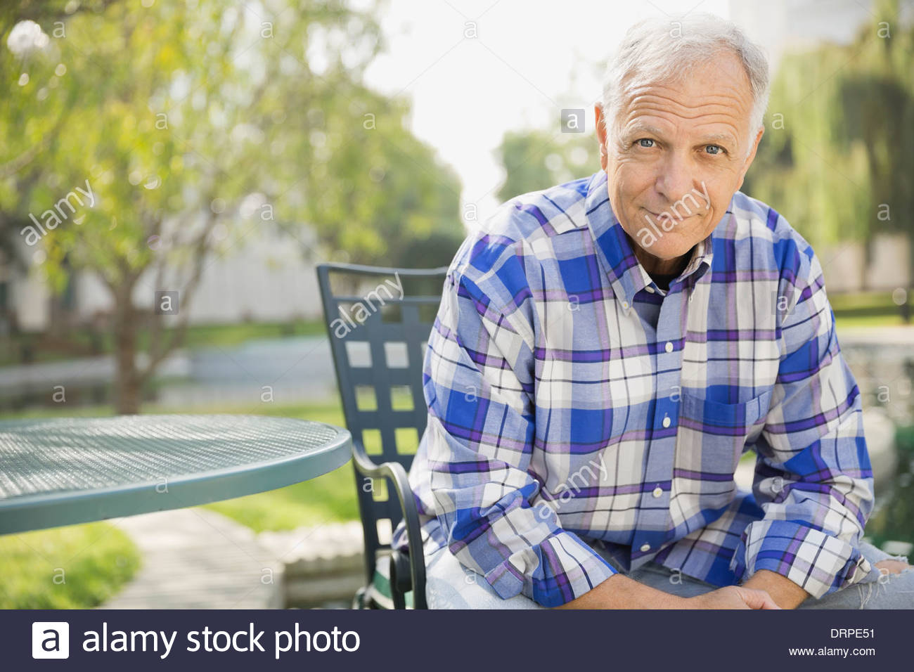 Portrait of senior man sitting outdoors - Stock Image