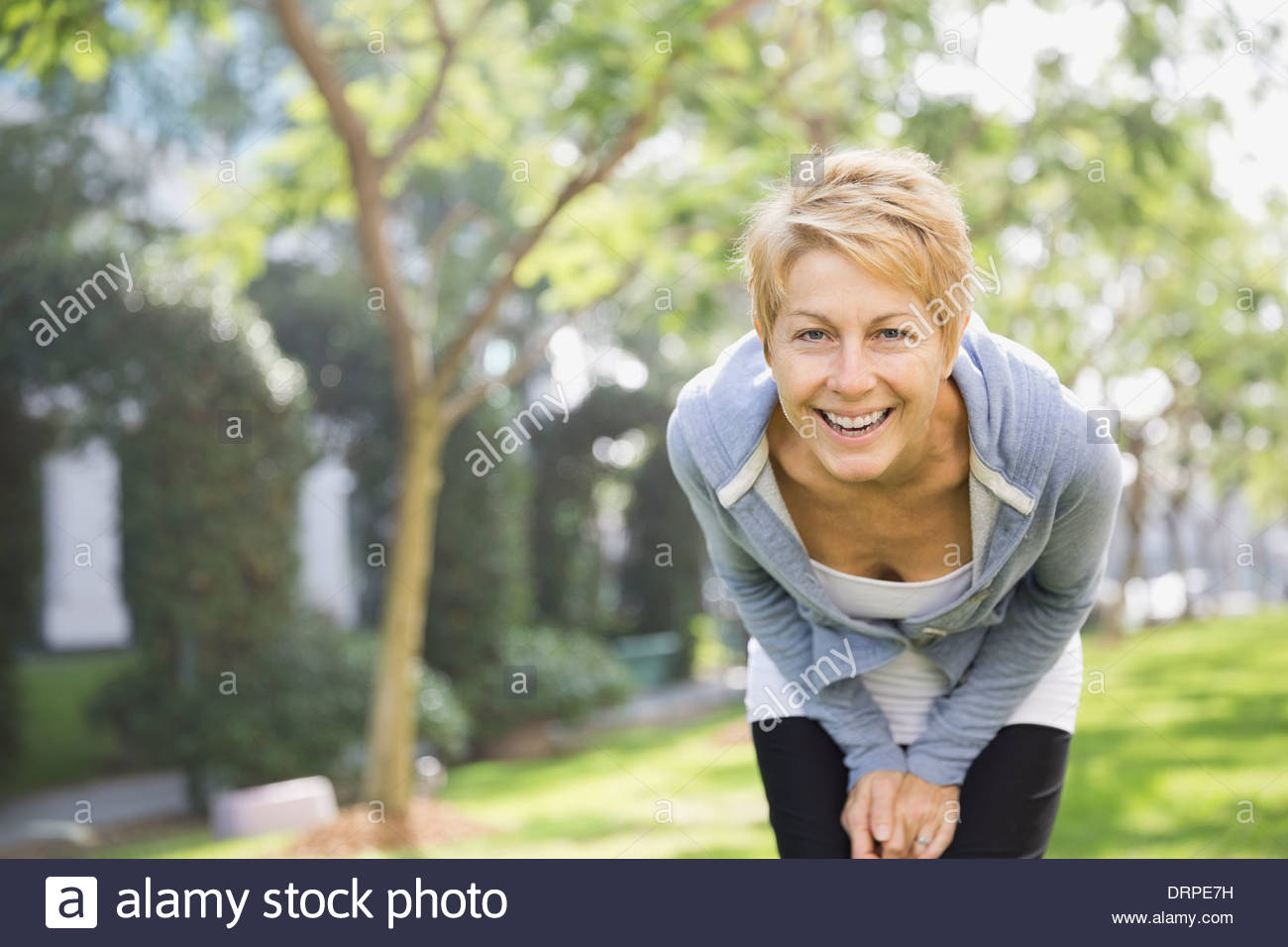 Portrait of cheerful woman in park - Stock Image