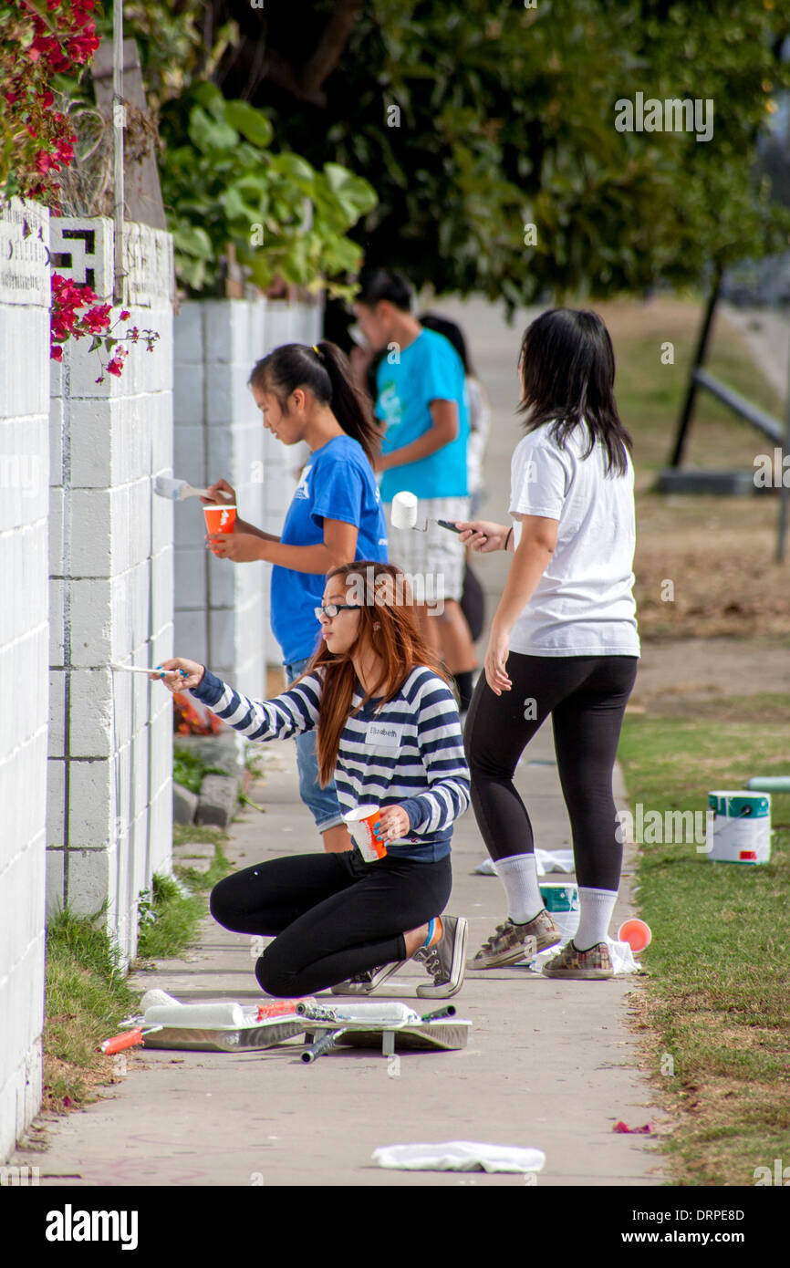 A volunteer team of Asian American teen girls repaints outdoor walls in a slum of Stanton, California, as part of a cleanup campaign. - Stock Image