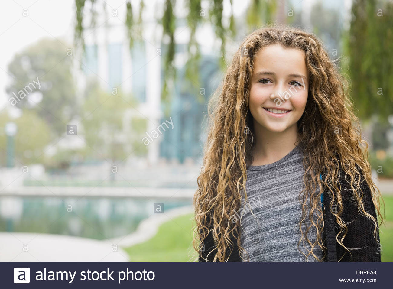 Portrait of smiling girl in park - Stock Image