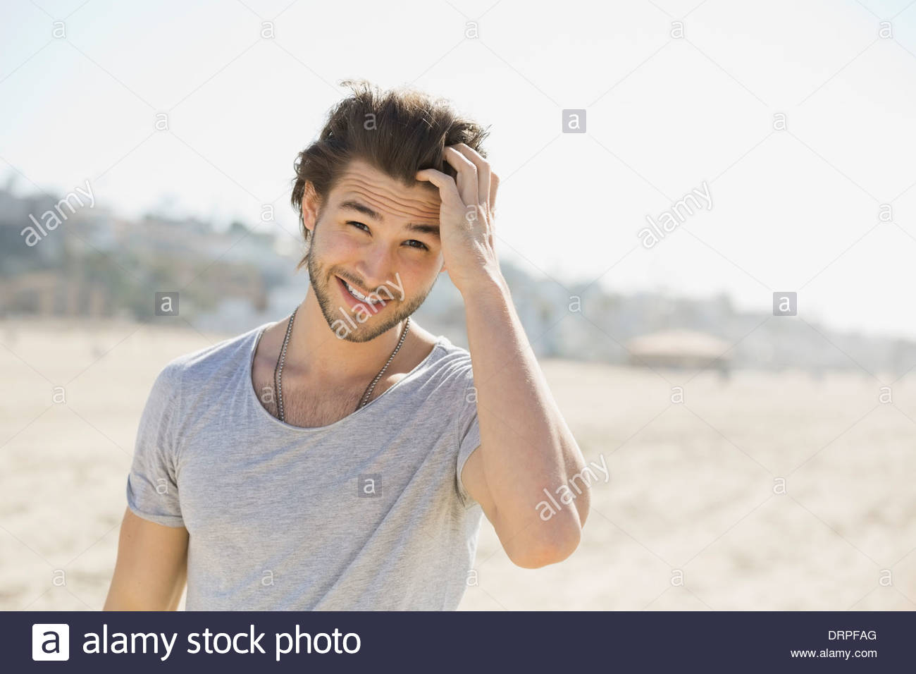 Portrait of man standing on beach - Stock Image