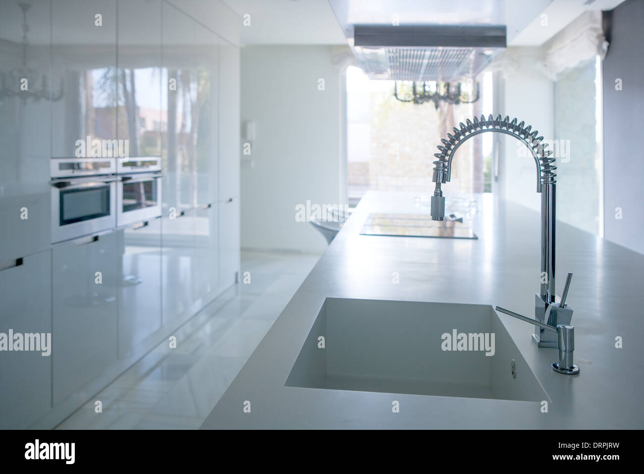 Modern white kitchen perspective with integrated bench sink and ...