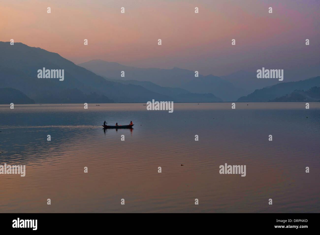 A lone boat sits on tranquil Phewa Lake in Phokara, Nepal - Stock Image