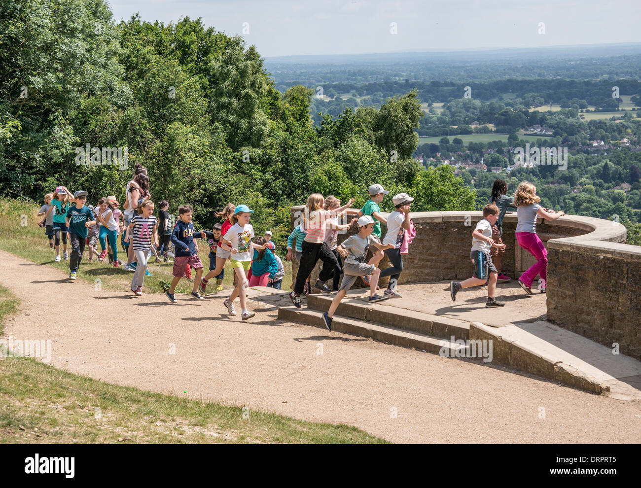 A class of excited schoolchildren, on an outing, rushing to take in the landscape view from a vantage point at Box Hill, Surrey, England, UK. - Stock Image