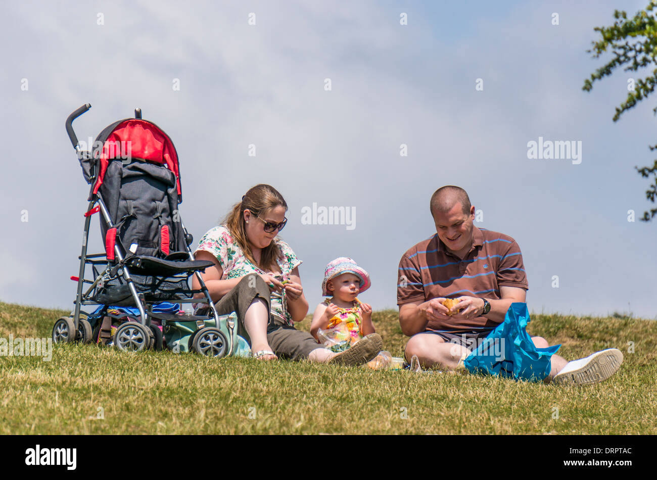 A couple and their baby spending some quality time together, having a picnic in the warm summer sunshine, on Box Hill, Surrey, England, UK. - Stock Image