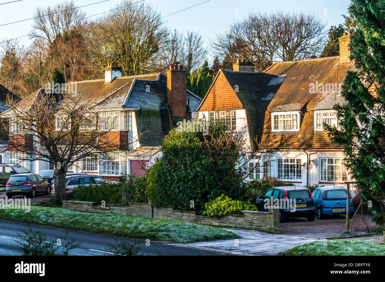 In outer London, a row of traditional 1930s houses, on a frosty winter morning, bathed in sunshine, in Epsom, Surrey, England, UK. - Stock Image