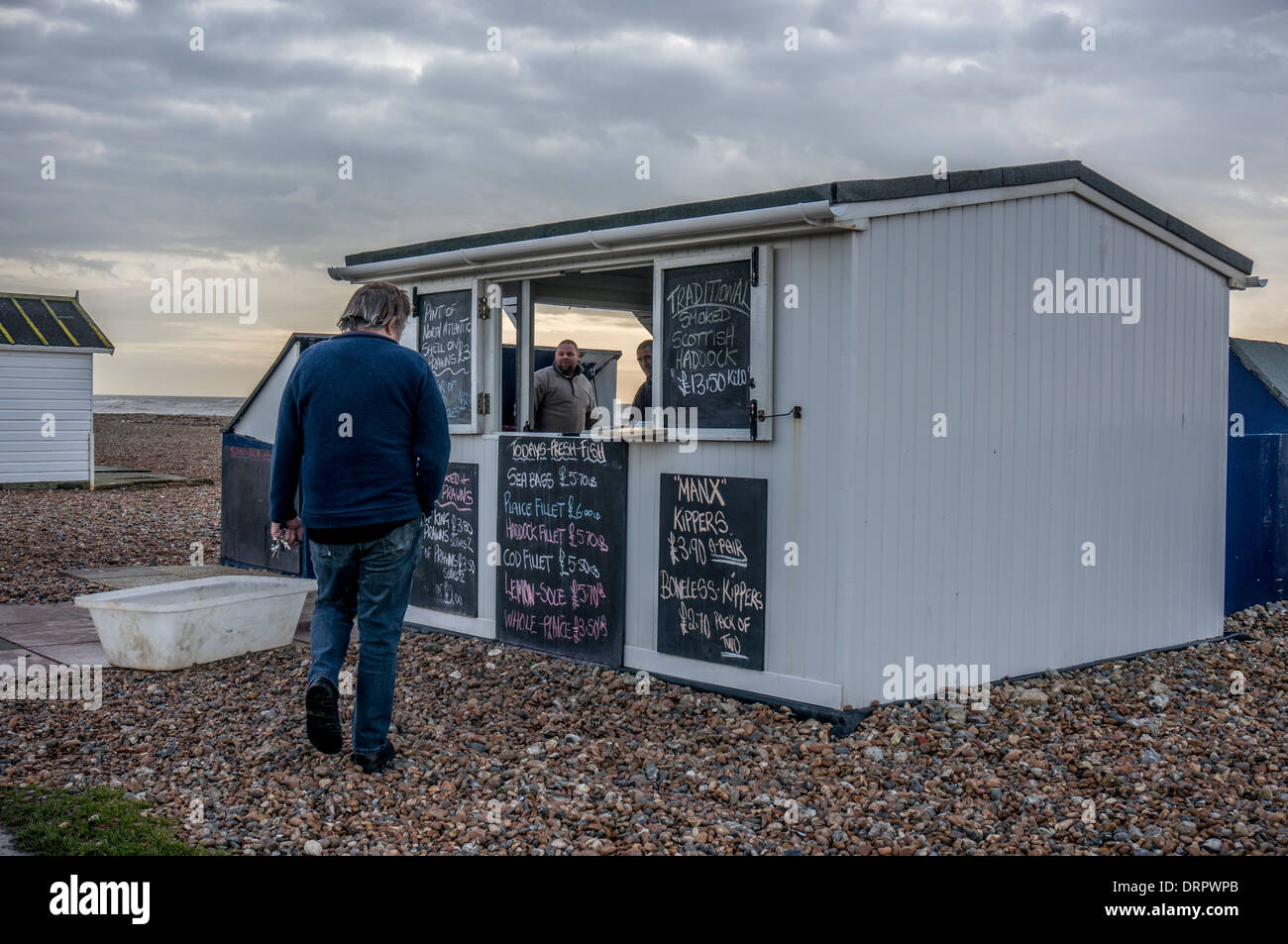 Man going to buy locally caught seafood from seller's hut on Goring-by-Sea pebble beach, near Worthing, West Sussex, England, UK. - Stock Image