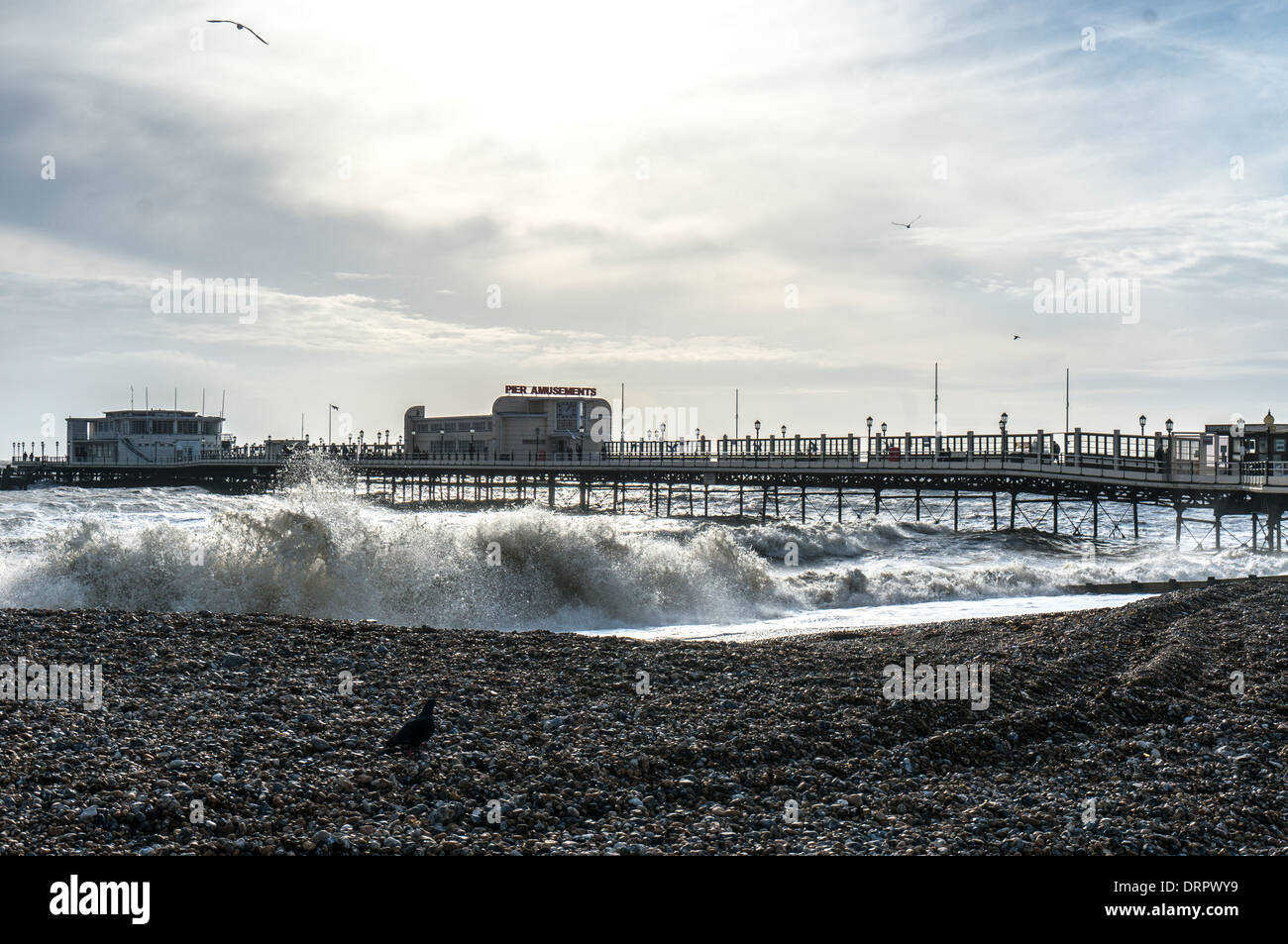 The pier with a deserted beach and stormy sea in winter, Worthing, West Sussex, England, UK. Stock Photo