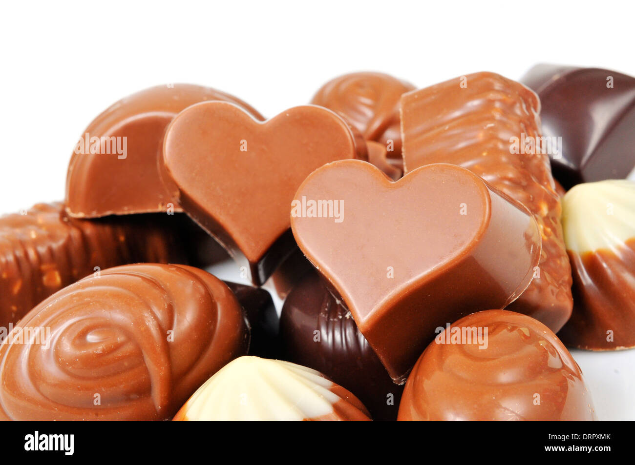 a pile of different chocolate bonbons, some of them heart-shaped, on a white background - Stock Image