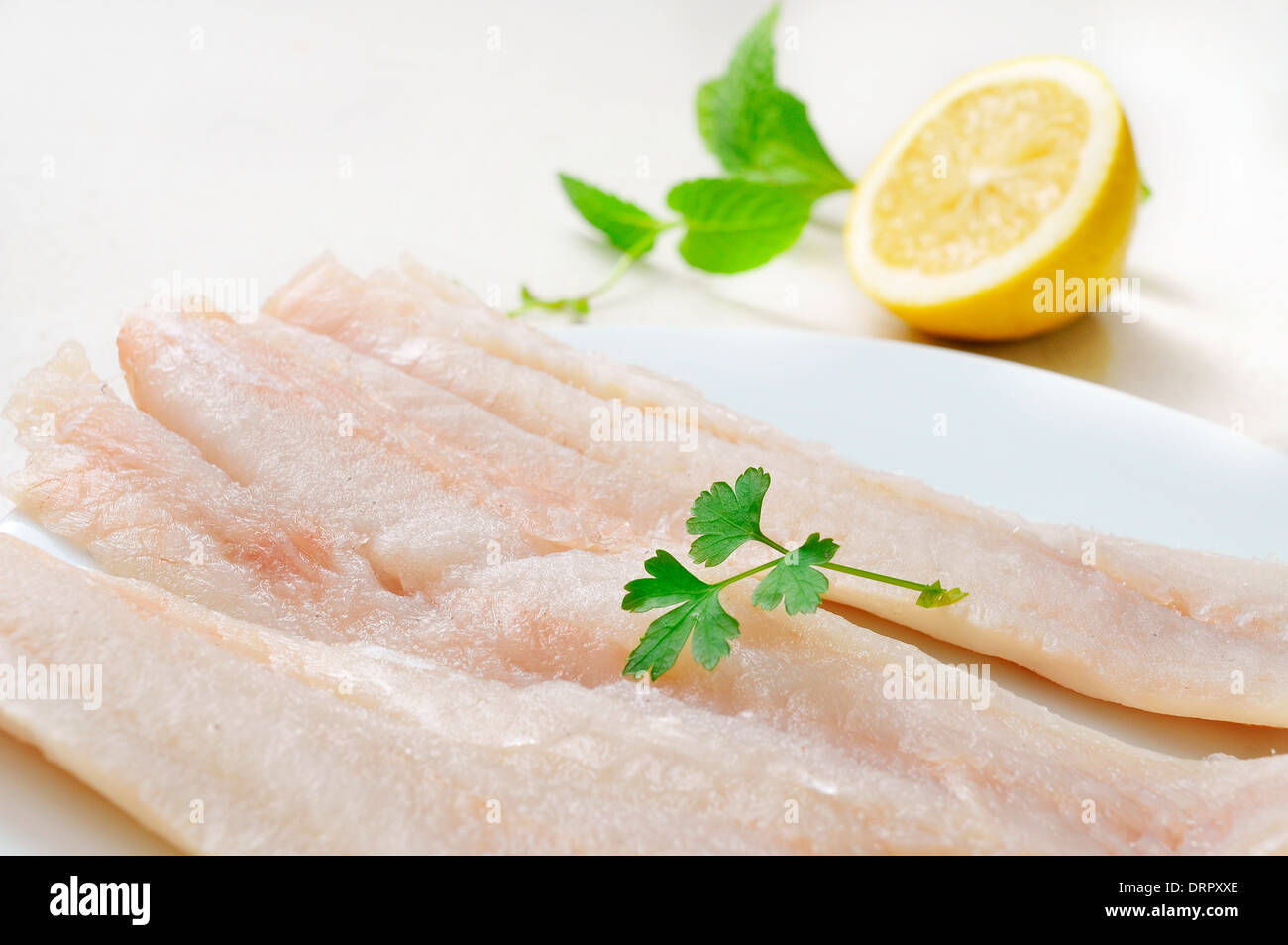 closeup of a plate with some raw pollack fillets - Stock Image