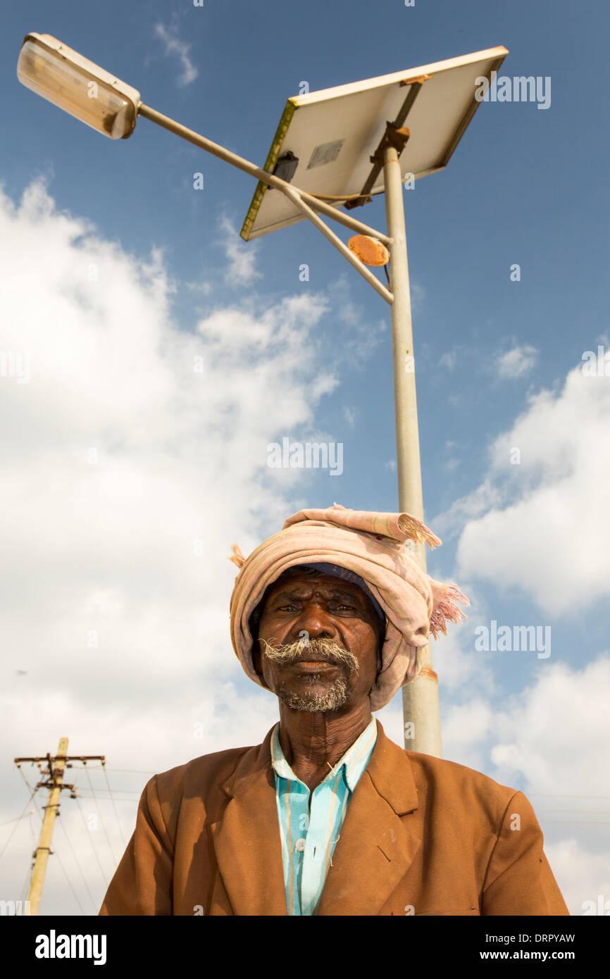 An old man underneath a solar street light in Karataka State near Mysore, India. - Stock Image