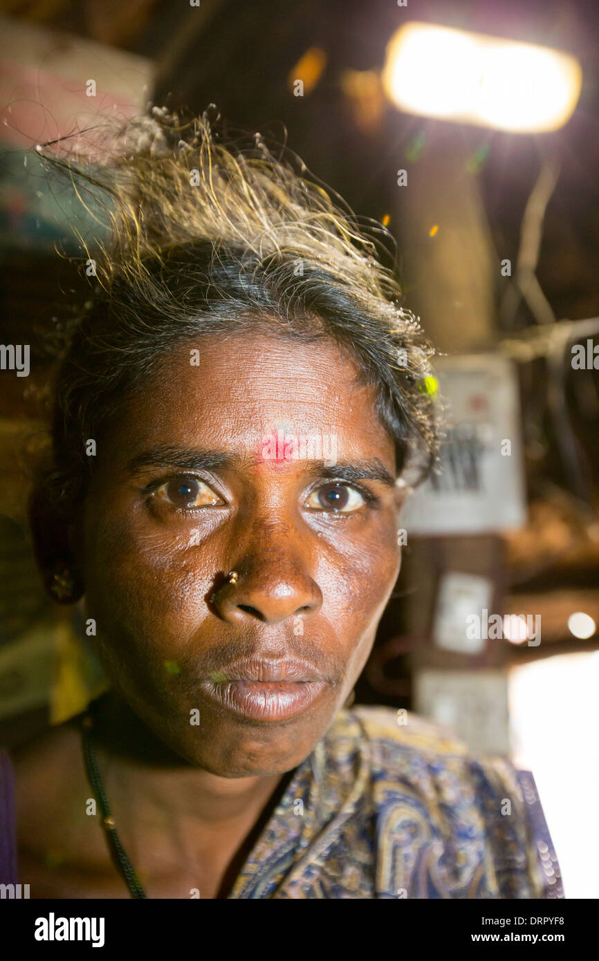 An untouchable woman in her hut, illuminated by an electric light, powered by an A4 sized solar panel, - Stock Image