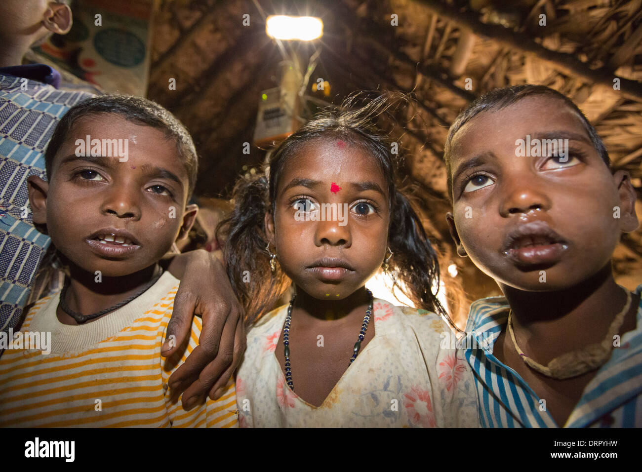 An untouchable family in their hut, illuminated by an electric light, powered by an A4 sized solar panel, - Stock Image