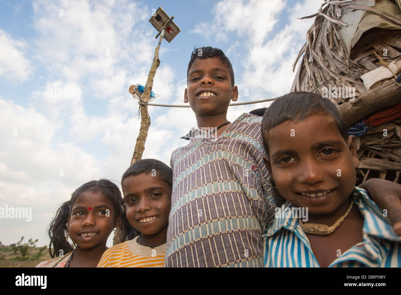 An untouchable family outside their hut, illuminated by an electric light, powered by an A4 sized solar panel - Stock Image