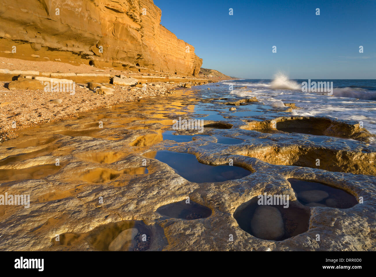 Exposed ledges and rockpools at Hive Beach, Burton Bradstock on the Jurassic Coast, Dorset, England. - Stock Image