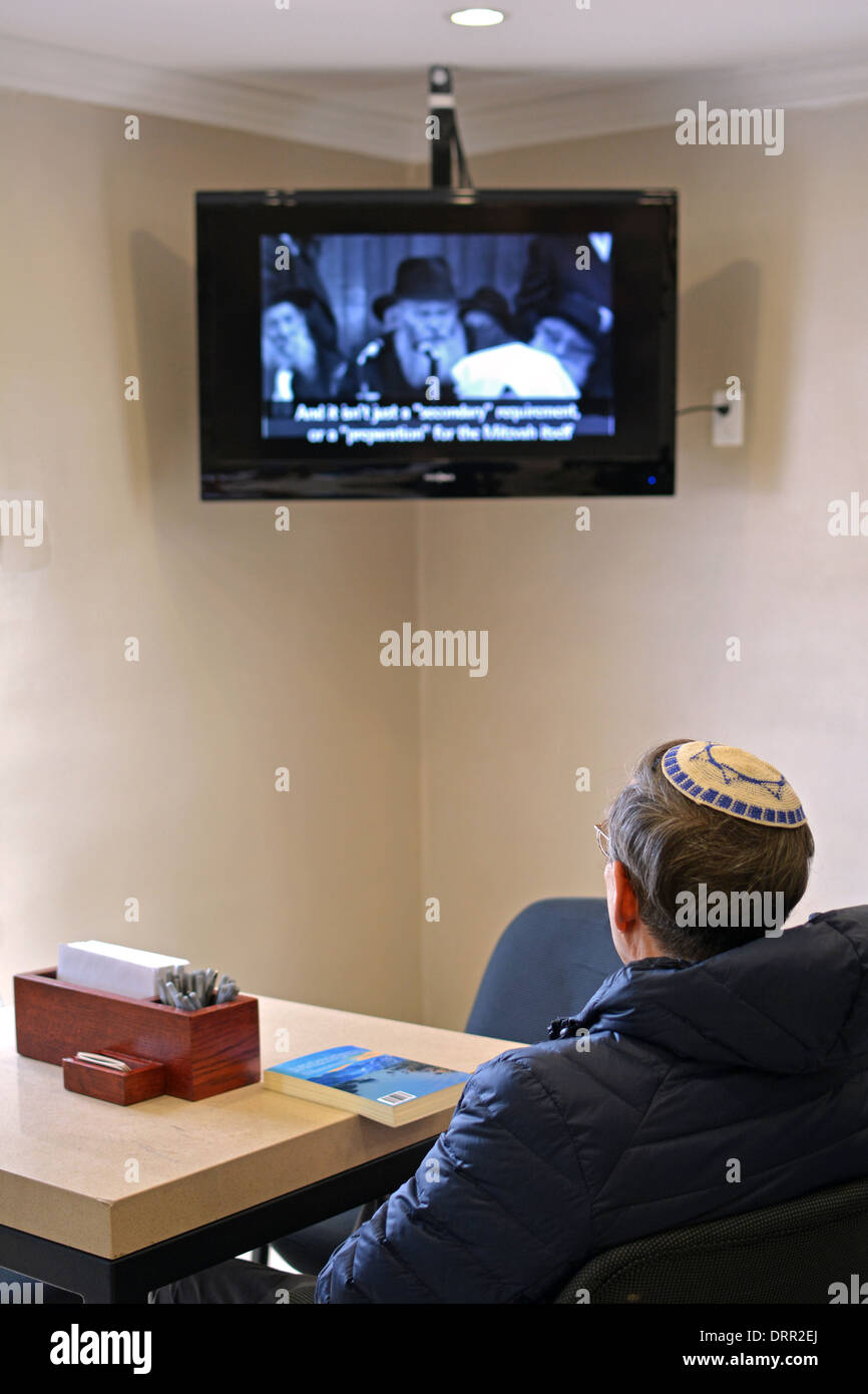 A religious Jewish man watching a video of a speech by the Lubavitcher Rebbe at the Ohel in Cambria Heights, Queens, - Stock Image