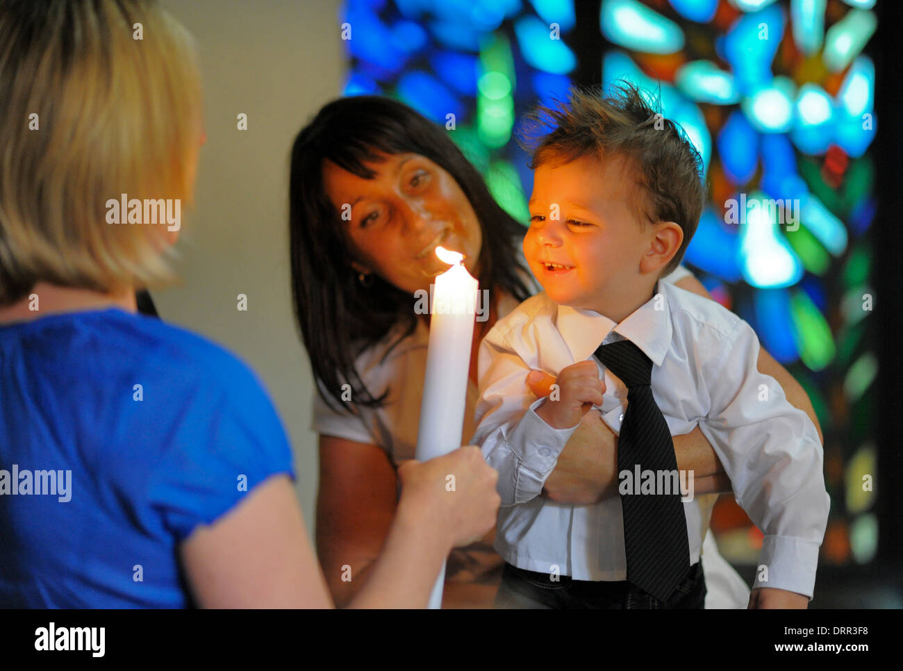 A boy blows out his baptism candle after his baptism. - Stock Image