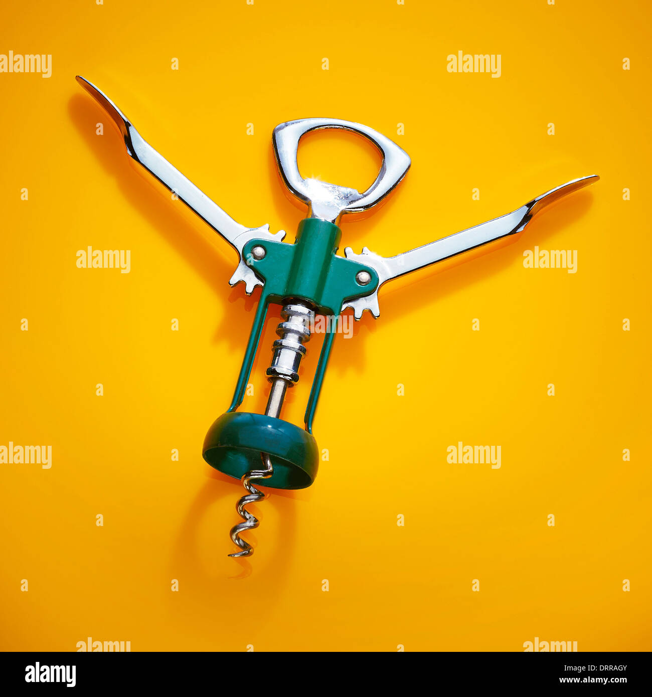 Chrome wine bottle opener on a yellow background - Stock Image