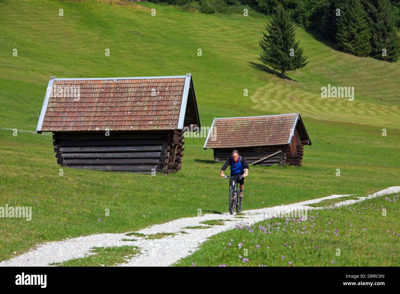 Elderly cyclist / mountain biker cycling past wooden huts / granaries along lake Gerold / Geroldsee near Mittenwald, Germany - Stock Image