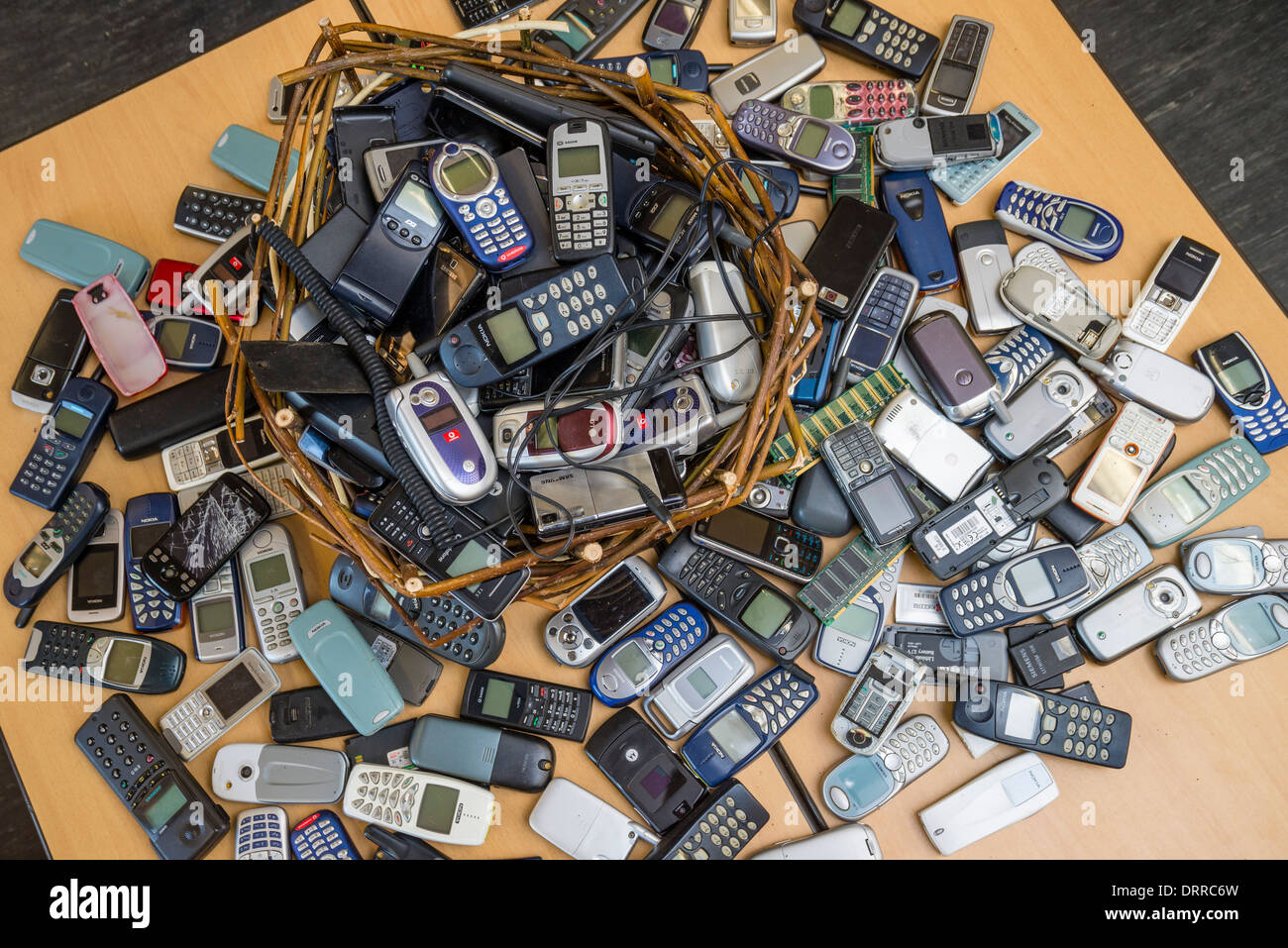 Discarded cellphones lie on a table. - Stock Image