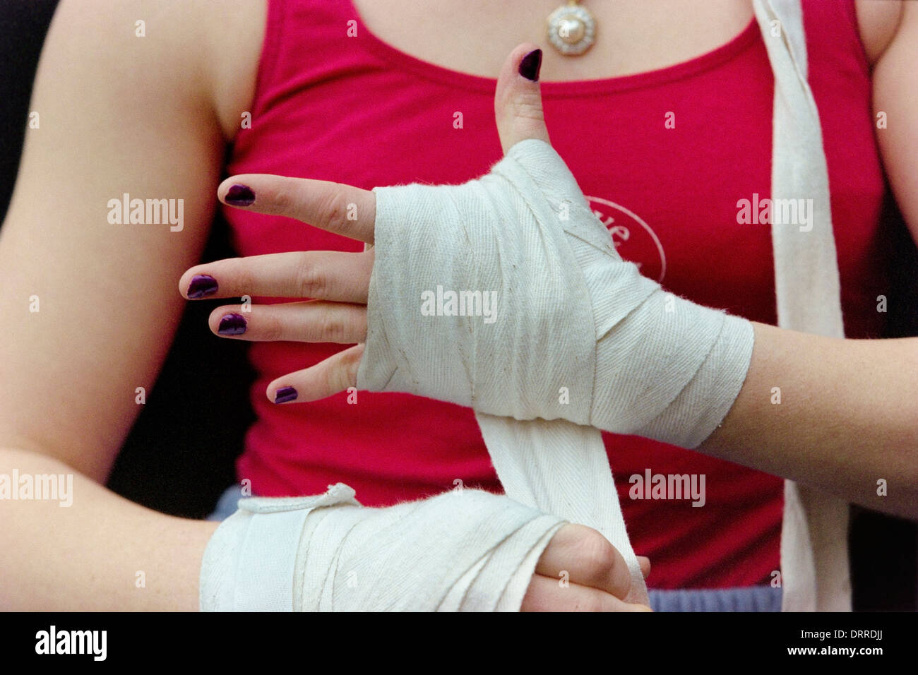 produse calde salvați foarte ieftin A female boxer wraps her hands in bandages before donning her ...
