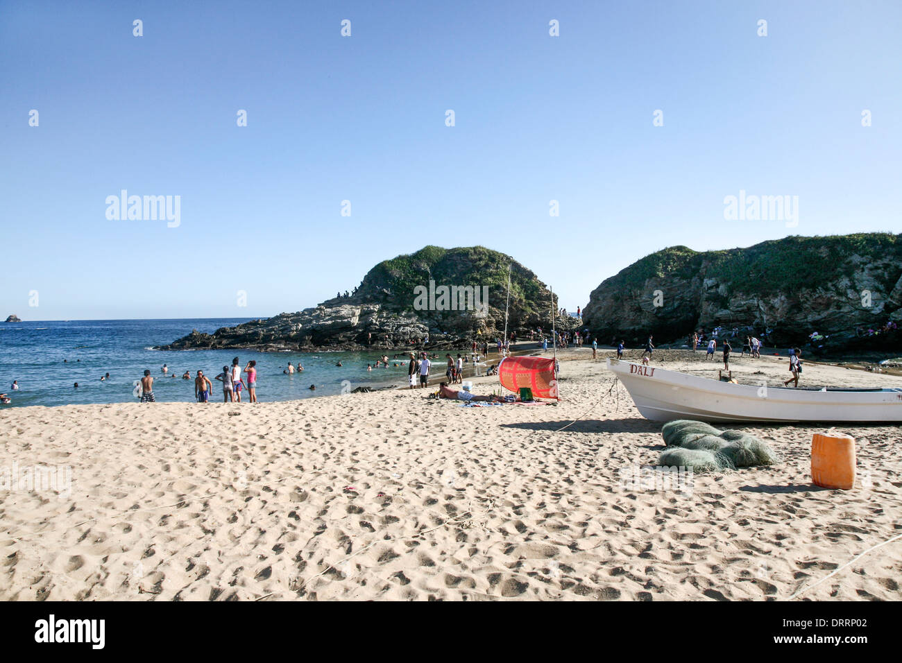 peaceful beach scene on hot Christmas day as Mexican families from neighboring towns enjoy cooling off in sea at San Agustinillo - Stock Image