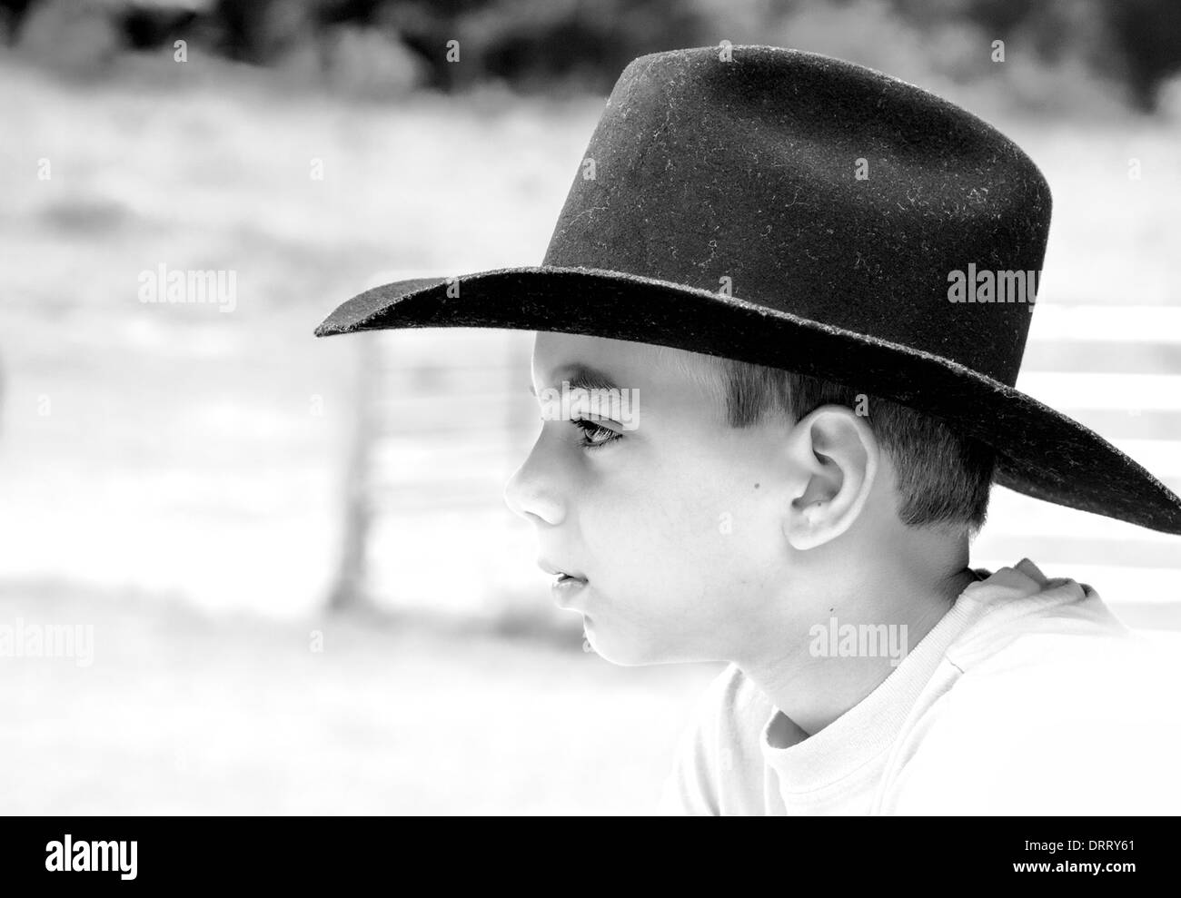61b6663a8b3a6 Black and White Portrait of young teen boy in black cowboy hat on ranch -  Stock