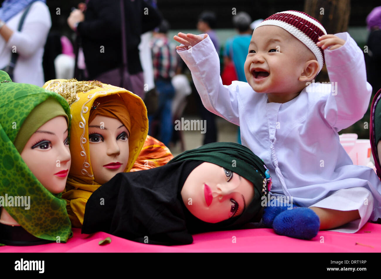 A boy plays with mannequin heads wearing hijabs during the celebration of World Hijab Day in Quezon City. - Stock Image