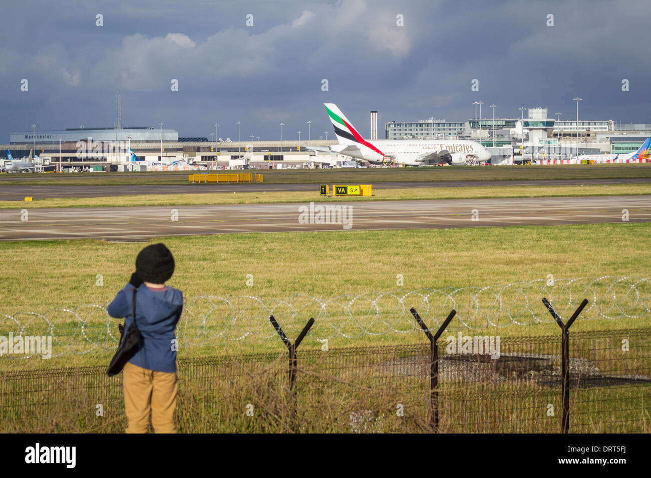 Young boy watching airplanes at Manchester Airport - Stock Image