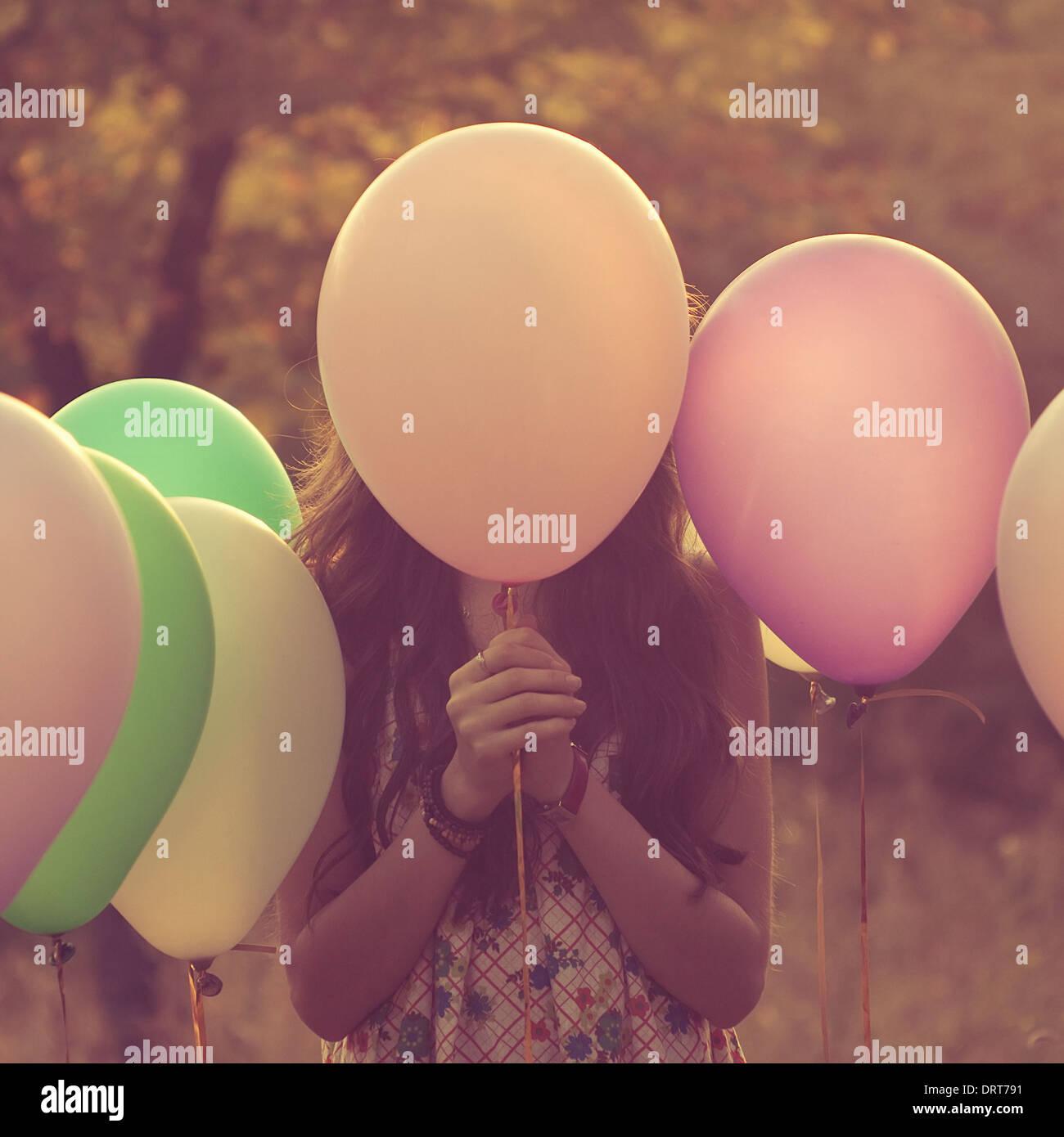 Girl hiding behind the balloon. Artistic portrait Stock Photo